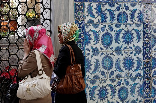 Stock Photo: 1848-222219 Two young Muslim women pray in front of the mausoleum of Mohammed´s standard_bearer Eyuep Ensari, Eyuep village, Golden Horn, Istanbul, Turkey