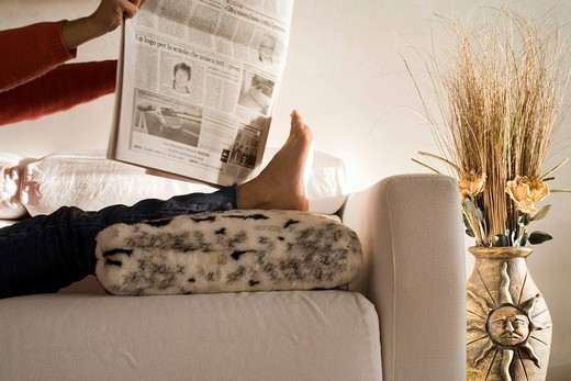 Woman reading a newspaper with feet on the couch pillow : Stock Photo