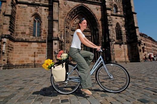 Woman goes shopping by bike, city centre of Nuremberg, Franconia, Bavaria, Germany, Europe : Stock Photo