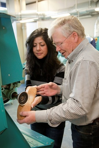 Specialist lecturer and Master Craftman student during the training using a grinder, Master course for orthopedic shoemakers, Master Craftman School of the Chamber of Small Industries and Skilled Trades, Dusseldorf, North Rhine_Westphalia, Germany, Europe : Stock Photo