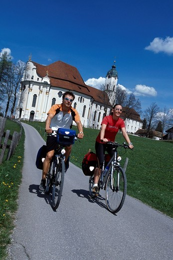 Two bikers pass the Wies church, Allgaeu, Bavaria, Germany : Stock Photo