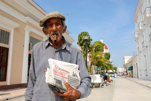 Old man wearing hat smoking a cigar, newspaper seller in Cienfuegos, Cuba, Caribbean : Stock Photo