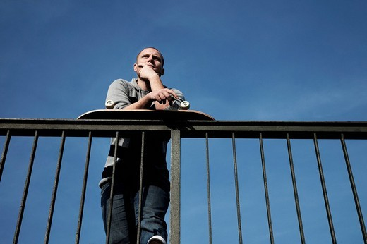 Stock Photo: 1848-233755 Young man with a skateboard on a railing