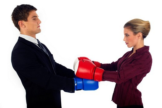 Man and woman wearing boxing gloves opposing each other : Stock Photo