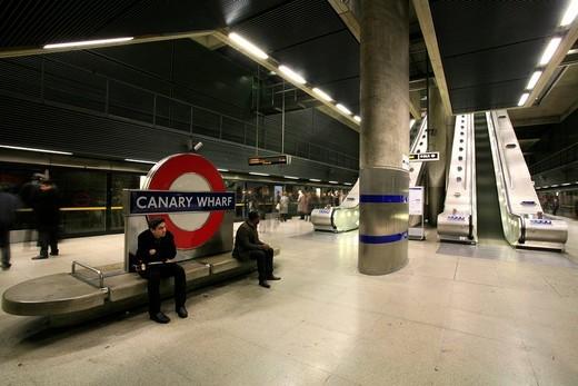 Escalators and waiting passengers at Canary Wharf underground station, London, England, UK, Europe : Stock Photo