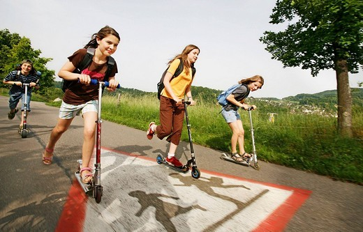 Stock Photo: 1848-235679 School children, boys and girls, riding kick scooters, push scooters over a ´caution_children´_traffic sign on the way from school, Basel, Switzerland, Europe