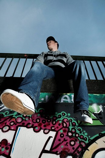 Young man sitting on a graffiti sprayed wall : Stock Photo