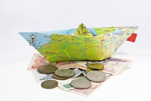 Foreign currency and a paper ship made from a map: symbol for international travel : Stock Photo
