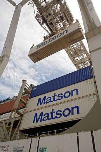 A crane loads shipping containers on the container ship Maui in the Port of Oakland, Oakland, California, USA : Stock Photo