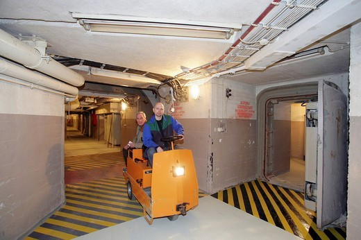 Employees driving an electric trolley through the corridors in the museum of the former Marienthal government bunker near Ahrweiler, Rhineland_Palatinate, Germany, Europe : Stock Photo