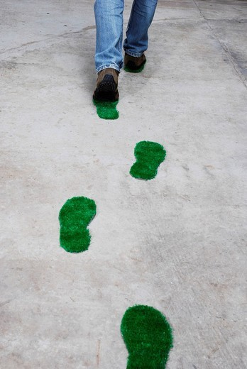 Stock Photo: 1848-241777 Man leaving green footprints over a concrete floor