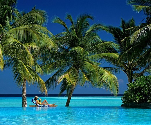 Young woman holding drink, laying on deck chair, swimming pool, ocean and palm trees, Sun Island, Ari Atoll, Maldives, Indian Ocean : Stock Photo