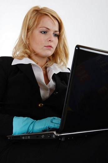 Housewife working on her laptop, wearing light blue rubber gloves : Stock Photo