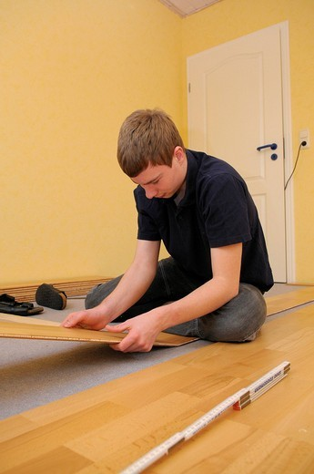 Teenager laying parquet flooring : Stock Photo