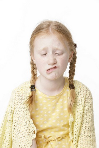 Eight_year_old girl wearing a yellow dress making a face : Stock Photo