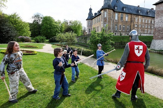 Children playing knights, sword fighting against a man dressed in a medieval knight?s armour and clothing during the Renaissancefest or Renaissance Festival at the moated castle Wasserschloss Dyck, Juechen, Rhineland, North Rhine_Westphalia, Germany, Euro : Stock Photo