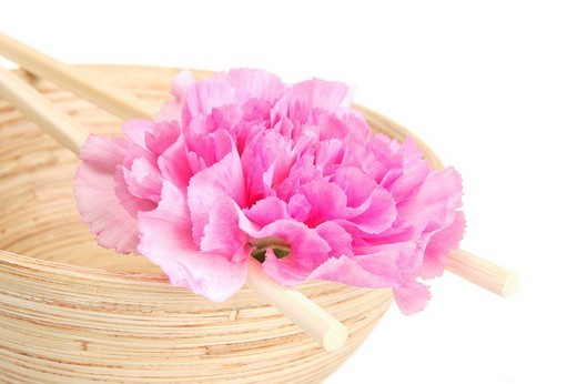 Wooden bowl with a carnation blossom and chopsticks : Stock Photo