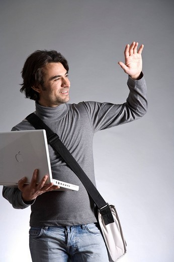 Young man with a bag, holding a laptop, waving : Stock Photo