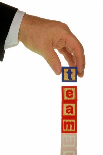 Manager using wooden blocks to write the word team : Stock Photo