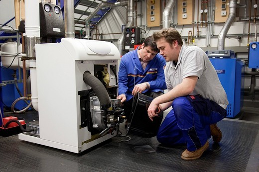 Specialist lecturer and Master Craftman for plumbing student in the heating, ventilating, and air conditioning, HVAC laboratory, controlling an oil heater, Master Craftman School of the Chamber of Small Industries and Skilled Trades, Dusseldorf, North Rhi : Stock Photo