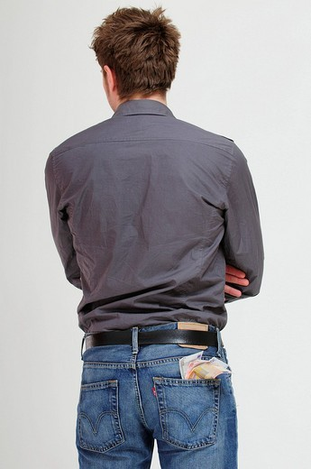 Young adult man, Euro bank notes poking out of the pocket of his jeans : Stock Photo