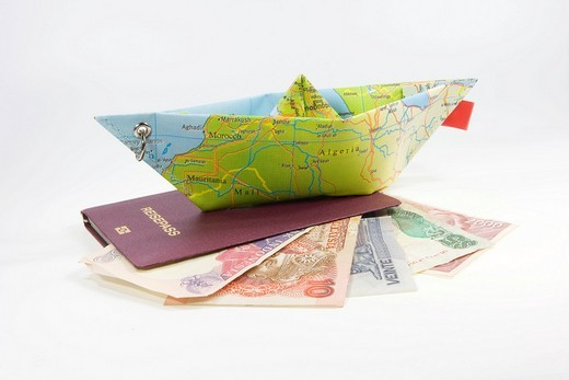 German passport, foreign currency and a paper ship made from a map: symbol for international travel : Stock Photo