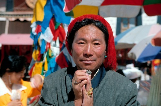 Tibetan man from the Kampha tribe with red hair knot, holding the symbol of the Tibetan snow lion as a trouser button with both hands, symbol contained in the Tibetan national flag, today banned in Tibet, Lhasa, Tibet, China, Asia : Stock Photo