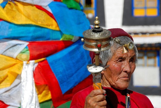 Stock Photo: 1848-252487 Tibetan woman with prayer wheel in her hand at colourful prayer flags Jokhang Kora Lhasa Tibet China