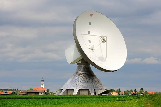 Parabolic antenna at the Erdfunkstelle, station for radio, television and data communications, with the spire of St. Remigius Church in Raisting, district of Weilheim_Schongau, Bavaria, Germany, Europe : Stock Photo