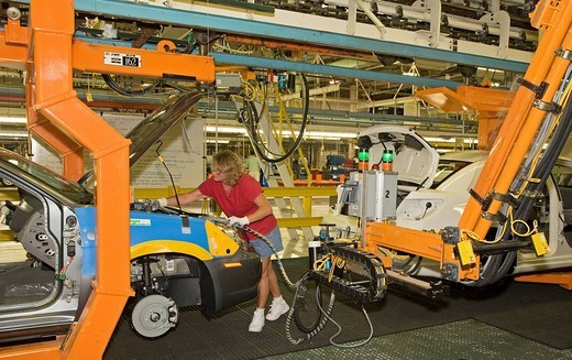 A member of the United Auto Workers union assembles the Chrysler Sebring sedan at Chrysler?s Sterling Heights Assembly Plant, here a worker hooks up hoses from a robot that will fill a new car with antifreeze and other fluids, Sterling Heights, Michigan,  : Stock Photo