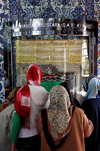 Devout Muslim women pray in front of a grave shrine, the mausoleum of Mohammed´s standard_bearer Eyuep Ensari, Eyuep village, Golden Horn, Istanbul, Turkey : Stock Photo