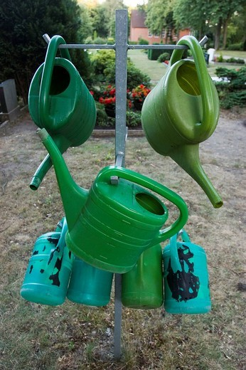 Watering cans at a cemetery : Stock Photo