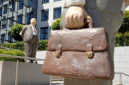 Sculpture of a businessman holding a briefcase in front of an office building in Munich, Bavaria, Germany : Stock Photo