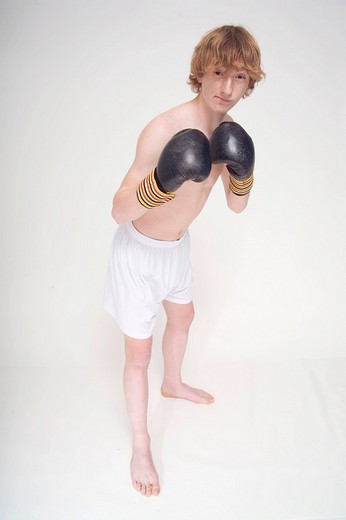 Stock Photo: 1848-257053 Thin, redheaded boy wearing boxing gloves, fighting stance