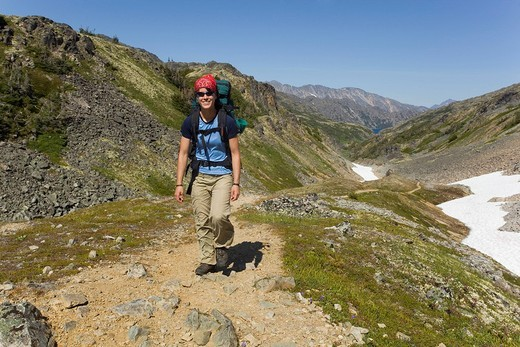 Young woman hiking, backpacking, hiker with backpack, historic Chilkoot Pass, Chilkoot Trail, snow field behind, alpine tundra, Yukon Territory, British Columbia, B. C., Canada : Stock Photo