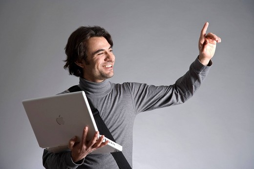Stock Photo: 1848-261738 Young man with a bag, holding a laptop, waving