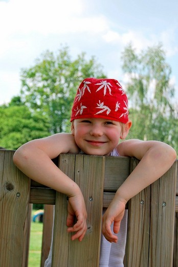 Stock Photo: 1848-261947 Girl, 5, wearing a red headscarf hanging over a garden fence like a young rascal
