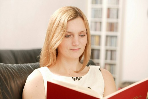 Young blonde woman reading red book : Stock Photo