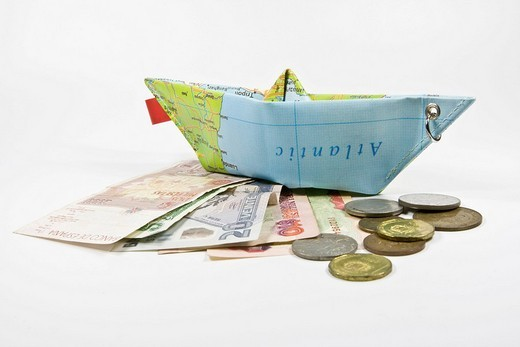 Foreign currency and a paper ship made from a map: symbol for international travel and currency exchange : Stock Photo