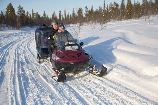 A women and a man in their forties on a snowmobile tour in Kiruna, Lappland, North Sweden, Sweden : Stock Photo