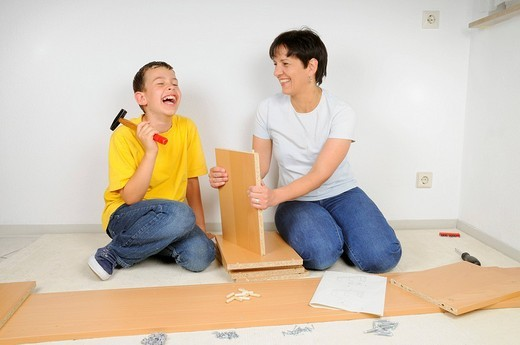 Mother and son assembling furniture, assembling the shelves : Stock Photo