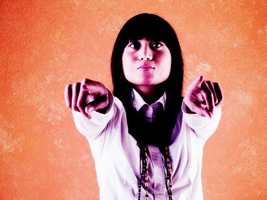 Stock Photo: 1848-268120 Young asian woman points with her fingers at the observer