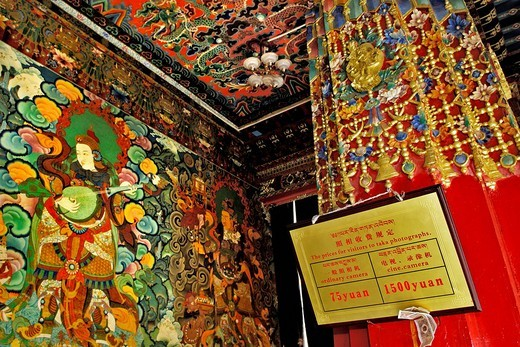 Wall and ceiling paintings, sign with prices for taking photos or making films, Jamkhang Chenmo monastery, Tashilhunpo, Tibet, Asia : Stock Photo