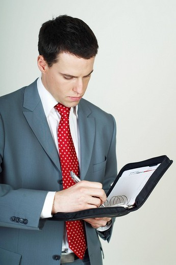 Young businessman taking notes, jotting in his agenda book : Stock Photo