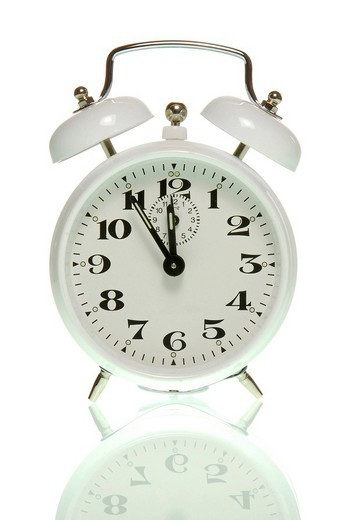 Alarm clock showing five to twelve, symbolic for high time : Stock Photo
