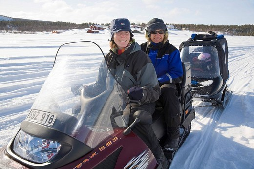 Two women in their forties on a snowmobile tour in Kiruna, Lappland, North Sweden, Sweden : Stock Photo