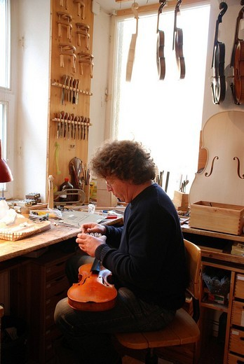 Luthier, violin maker in his workshop : Stock Photo