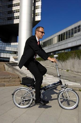 Businessman on his way to work on a folding bike, Hypobank building, Bogenhausen, Munich, Bavaria, Germany, Europe : Stock Photo