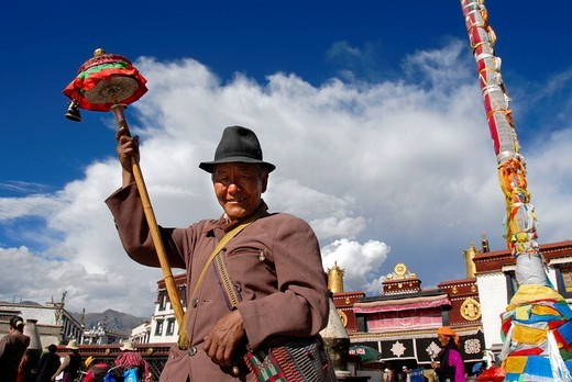 Tibetan man with prayer wheel in his hand at the main entrance of Jokhang Kora Lhasa Tibet China : Stock Photo