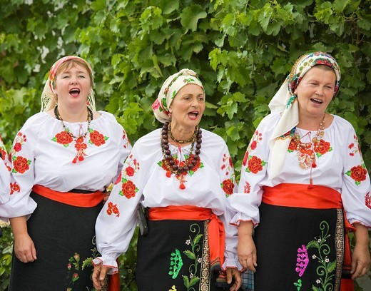 Three peasant women in traditional Ukrainian costume performing a countrified folk dance at the farmers´ museum in the formerly German inhabited Bessarabian village Friedenstal, today´s Mirnopolje, Ukraine : Stock Photo